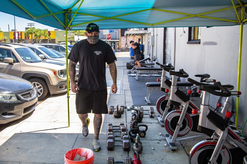Personal trainer, William Jones, watches over the equipment placed on the sidewalk for gym members.