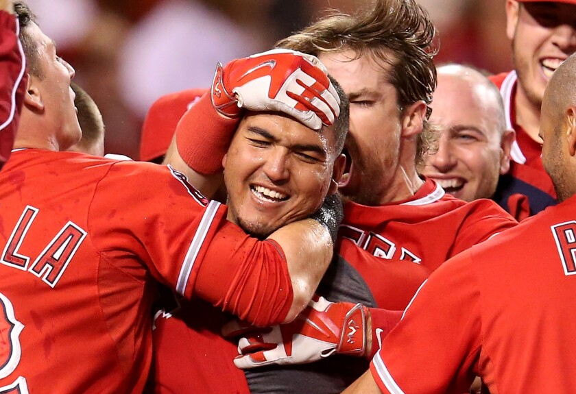 Catcher Carlos Perez is mobbed by his Angels teammates after hitting a walk-off home run in his major league debut. The Angels beat the Seattle Mariners, 5-4.