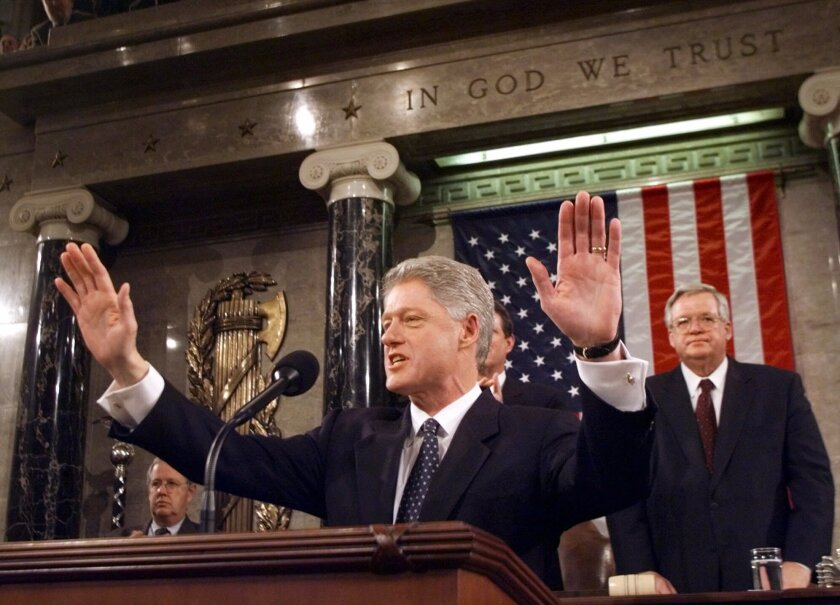 FILE - In this Jan. 19, 1999 file photo, President Clinton acknowledges the crowd prior to giving his State of the Union address on Capitol Hill . House Speaker Dennis Hastert of Illinois is at right. Two decades ago, President Bill Clinton delivered his State of the Union address before a nation transfixed by his impeachment. He didn't use the I-word once. President Donald Trump is far from the first president to deliver a State of the Union address in a time of turmoil. (AP Photo/Win McNamee, Pool, File)