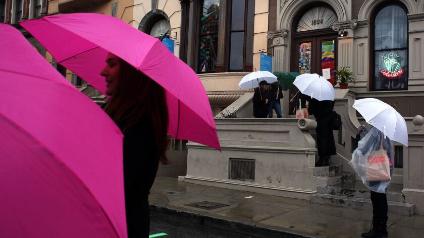 """With pink Frieze umbrellas shielding them from rain on the Paramount studio back lot, people attending the art fair's Thursday preview walk past Lisa Anne Auerbach's """"Psychic Art Advisor."""""""