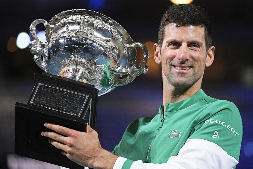 Novak Djokovic smiles and holds up a trophy.