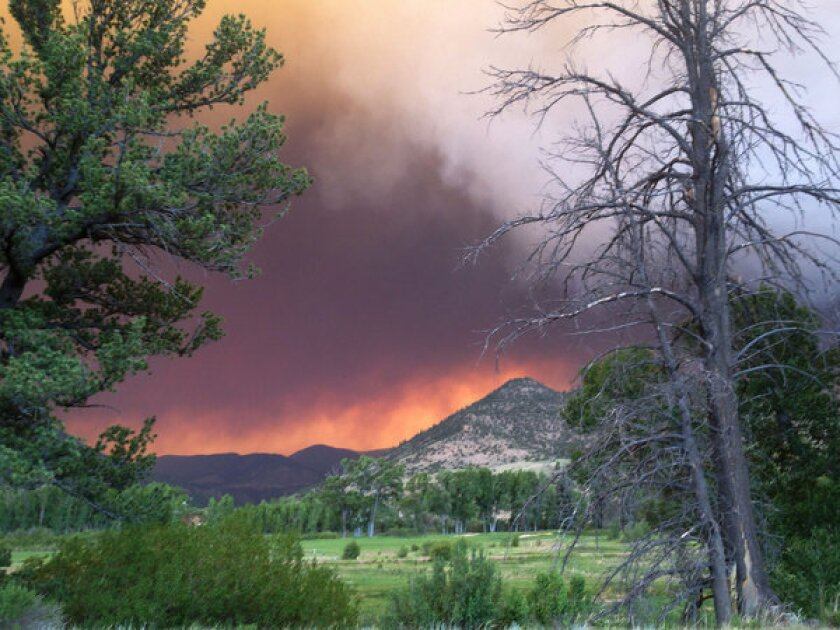 Wildfires approach the town of South Fork, Colo., on Thursday. The town was evacuated Friday morning.