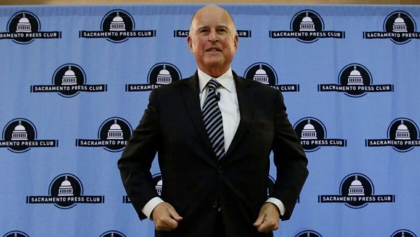 Gov. Jerry Brown smiles after his appearance at the Sacramento Press Club on Dec. 18.