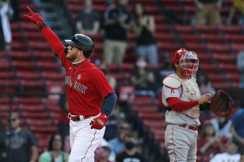 Boston Red Sox's Alex Verdugo, left, celebrates his solo home run as Los Angeles Angels' Kurt Suzuki stands at home plate during the first inning of a baseball game, Saturday, May 15, 2021, in Boston. (AP Photo/Michael Dwyer)