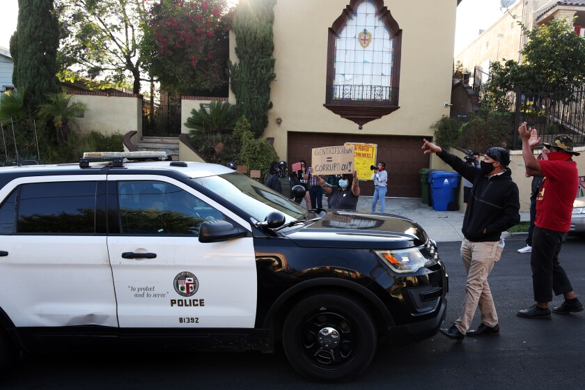 Protestors prevent a police car from passing through while outside Councilman Jose Huizar's home in Boyle Heights