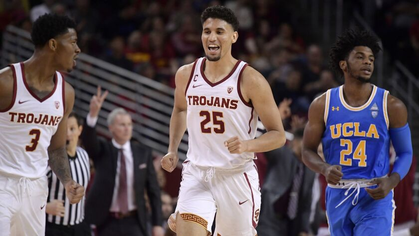 USC forward Bennie Boatwright, second from right, celebrates with guard Elijah Weaver, left, after scoring as UCLA guard Jalen Hill, right, runs behind and USC head coach Andy Enfield gestures during the second half.