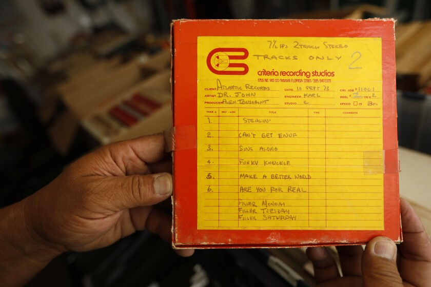 Collector Mike Nishita holds a copy of a box that contains a tape of recordings by Dr. John, produced by Allen Toussaint.