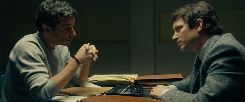 Two men face each other across a desk.