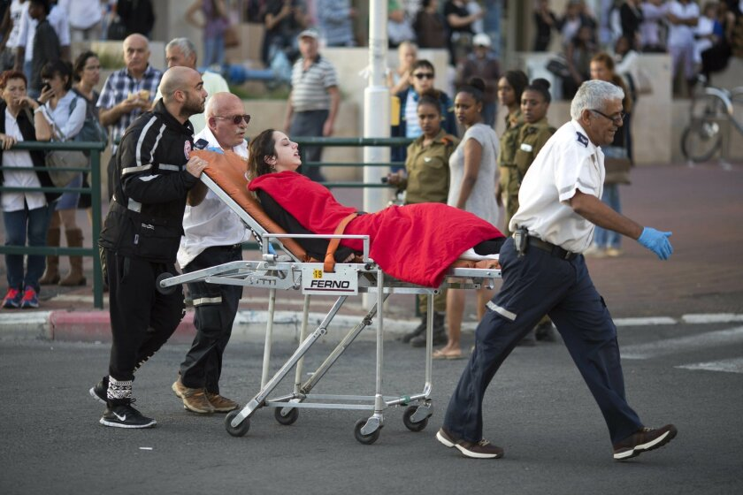 FILE - In this Monday, Nov. 2, 2015 file photo, Israeli rescue personal evacuate a woman after a stabbing attack in Rishon Lezion, Israel. After years of relative quiet in major Israeli cities, a seven-week burst of violence has brought the Palestinian issue back to the country's heartland and push