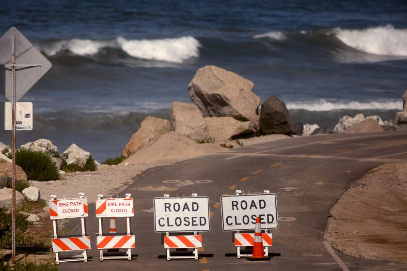 Waves are minus surfers next to a closed bike path in Manhattan Beach.