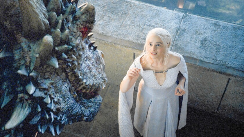 """Daenerys Targaryen (Emilia Clarke) greets one of her dragons -- no longer mere youngsters -- in the new season of """"Game of Thrones."""""""