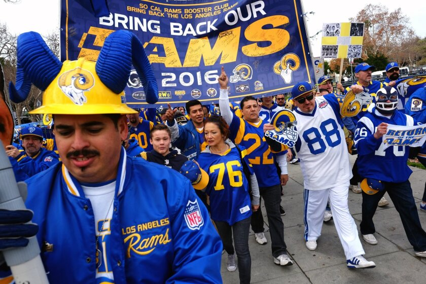 Rams football fans hold banners, wave signs and chant while marching around the L.A. Memorial Coliseum in January.