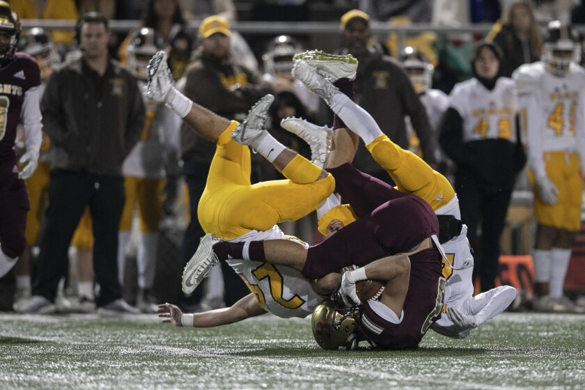 Bishop's receiver Clay Petry (dark jersey) is tackled by El Camino's Alex Arellano (left) and Nathan Musgrove during the Division II championship game Friday at Southwestern College.