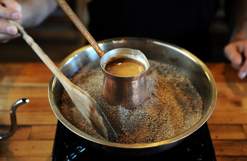 Stan Mayzalis makes jazzve-style coffee on a bed of hot sand at Doma Kitchen in Manhattan Beach.