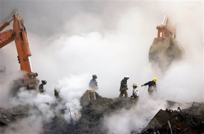 FILE - In this Oct. 11, 2001 file photo, firefighters make their way over the ruins of the World Trade Center through clouds of dust and smoke at ground zero in New York. With the Oct. 3, 2013 deadline looming, more than 32,000 people have applied to the federal compensation fund for people with il