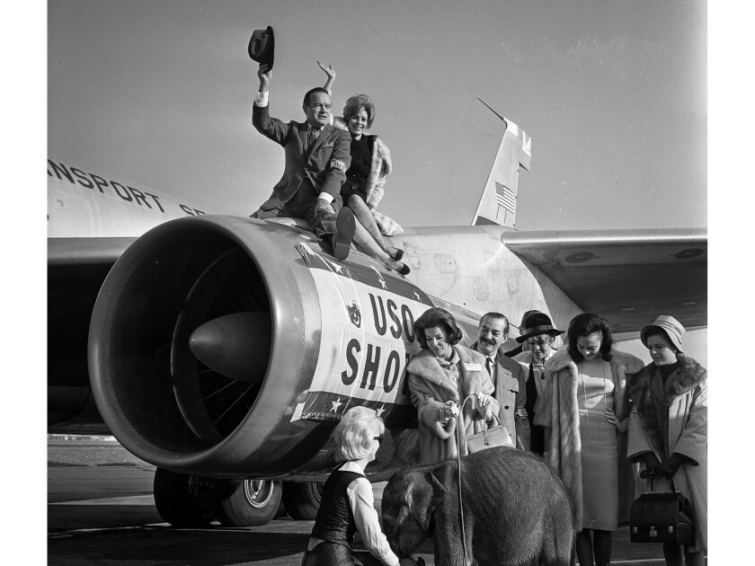 Dec. 15, 1964: Bob Hope and actress Jill St. John perch on a jet engine before flying from Los Angeles International Airport to Southeast Asia.