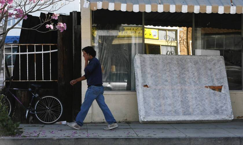 A discarded box spring is propped against a vacant store on Avalon Boulevard in Wilmington. California lawmakers are jousting with mattress makers over proposed recycling legislation.