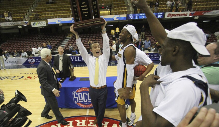 Chattanooga coach Matt McCall celebrates with his team after winning the Southern Conference men's basketball championship against East Tennessee State University in Asheville, N.C.