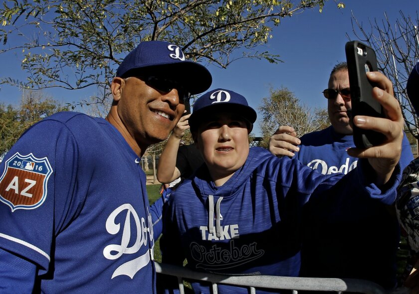 Bryan Cruz takes a selfie with Los Angeles Dodgers manager Dave Roberts during a spring training baseball workout Saturday, Feb. 20, 2016, in Glendale, Ariz. (AP Photo/Morry Gash)
