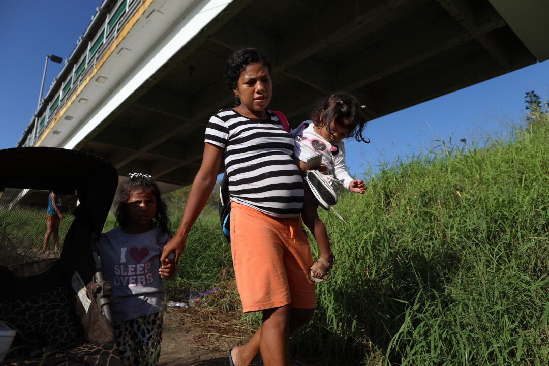 A woman with two young girls under a bridge.