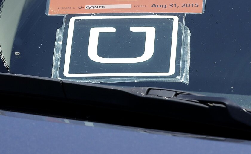 FILE - In this Wednesday, July 15, 2015, file photo, an Uber sign is displayed on a driver's car parked near the San Francisco International Airport parking area in San Francisco. (AP Photo/Jeff Chiu, File)