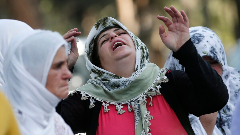 Relatives of bombing victims mourn in front of a forensic medicine center in Gaziantep, Turkey.