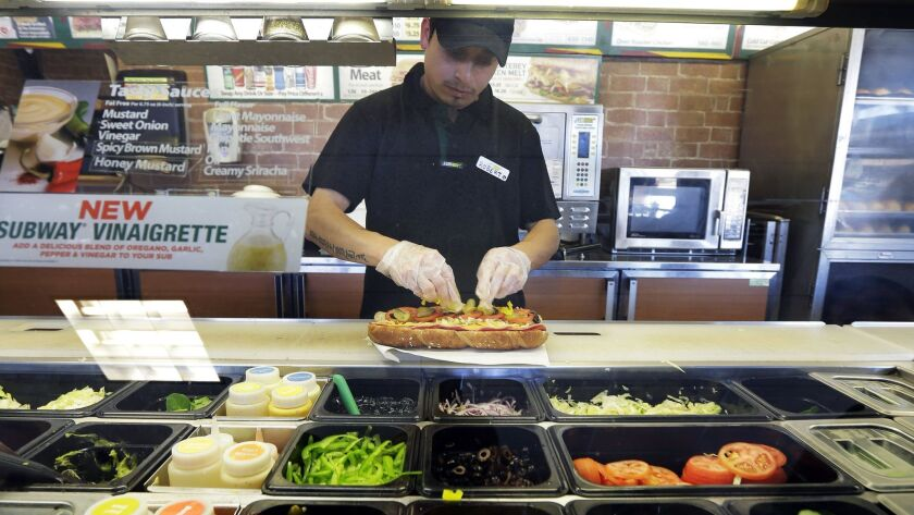 A worker makes a sandwich at a Subway sandwich franchise in Seattle on March 3, 2015.