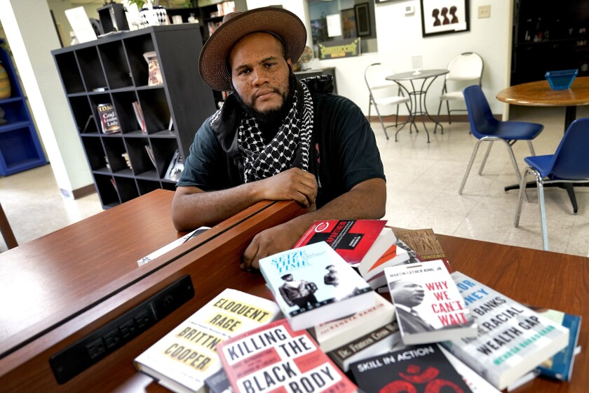 Owner Ali Nervis displays books on race relations at his bookstore in Phoenix