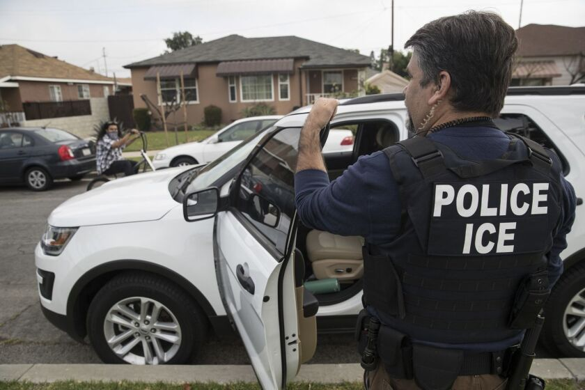An ICE agent surveys a Montebello neighborhood in April 2017.