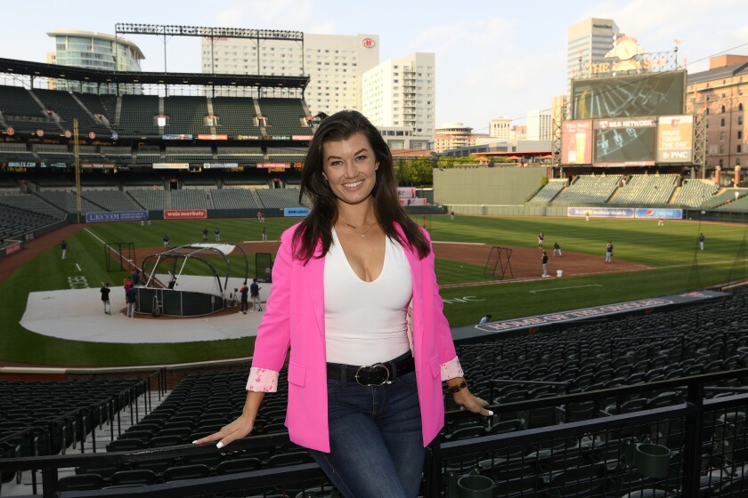 Baltimore Orioles radio and TV announcer Melanie Newman poses for a photograph before a baseball game at Oriole Park at Camden Yards, Tuesday, Sept. 28, 2021, in Baltimore. Newman made history earlier this season when she was part of Major League Baseball's first all-women's broadcast. On Wednesday, the Orioles announcer will receive a bigger national stage when she teams up with Jessica Mendoza on ESPN. (AP Photo/Nick Wass)