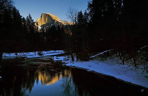Yosemite National Park's Half Dome is reflected in the Merced River in this view from Sentinel Bridge. Members of the Civilian Conservation Corps replaced climbing cables on the mountain, among other projects in the park.