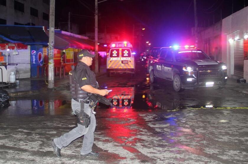 Policías ministeriales resguardan la zona, donde se registró un ataque armado, al interior de un bar el la Ciudad de Cancún, Quintana Roo (México). EFE