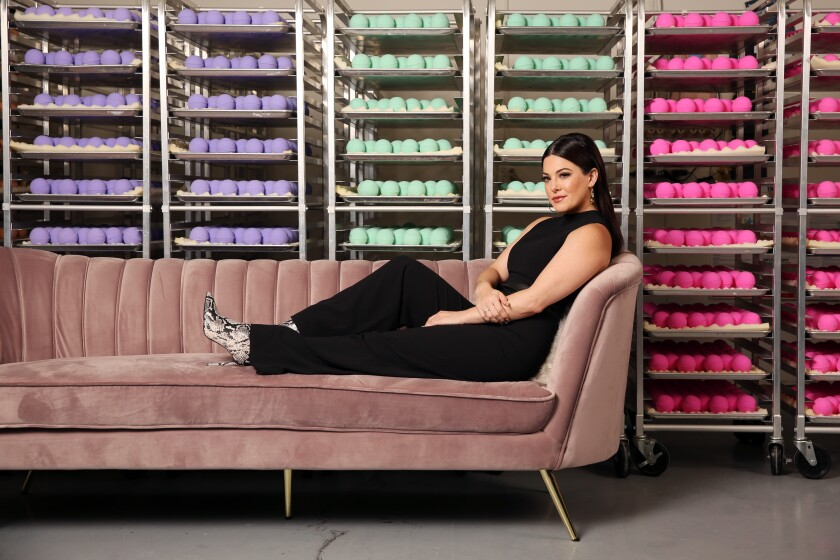 Olivia Alexander, founder and chief executive of Kush Queen, at the company's headquarters in Anaheim, framed by racks of bath bombs infused with CBD.