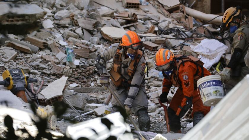 Firefighters try to find survivors amid the debris of two buildings that collapsed in Muzema neighbo