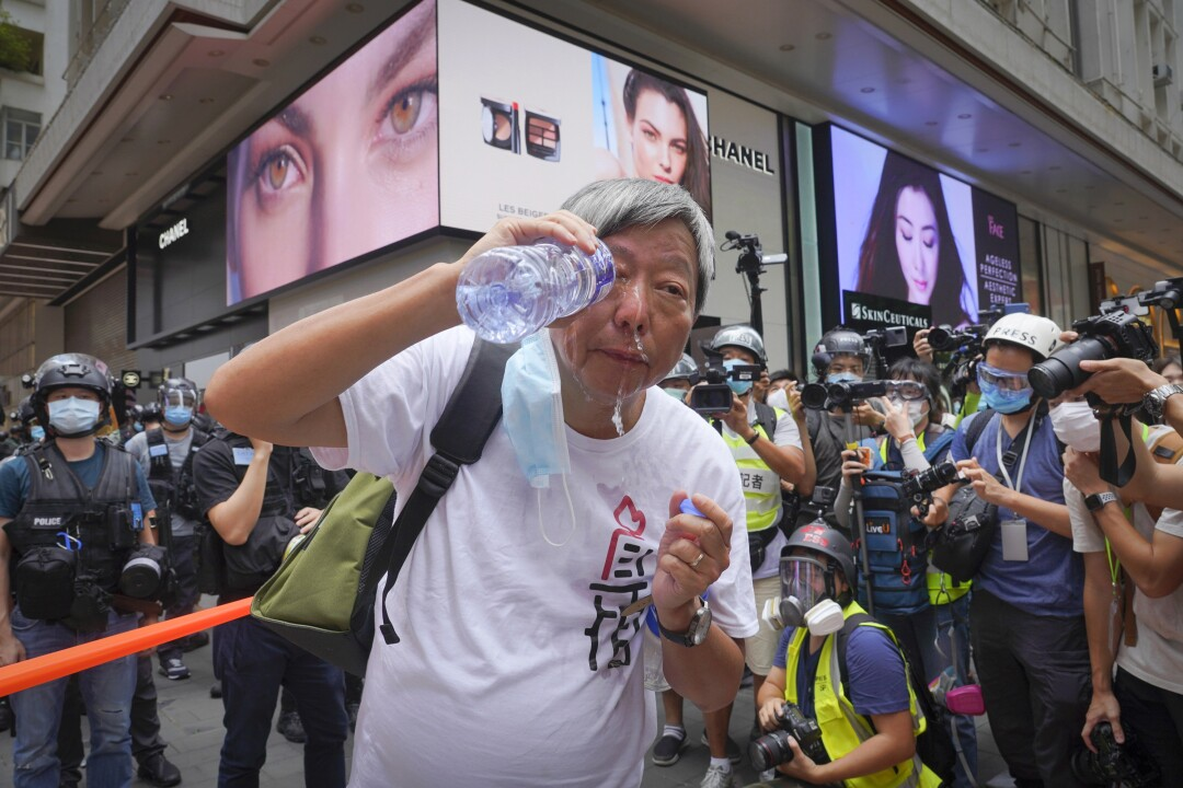 Lee Cheuk-yan washes his eyes with water after being pepper sprayed by Hong Kong police during a demonstration Wednesday.