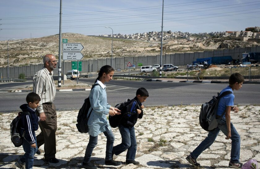 In this photo taken Monday, April 21, 2014, Ahmed Khatib walks with four of his six children along the separation barrier between the West Bank village of Hizme and the city of Jerusalem. The Khatibs are being kept apart by Israeli restrictions on Palestinian movement in east Jerusalem, including a towering separation barrier of cement slabs that cuts through families and neighborhoods. (AP Photo/Nasser Shiyoukhi)