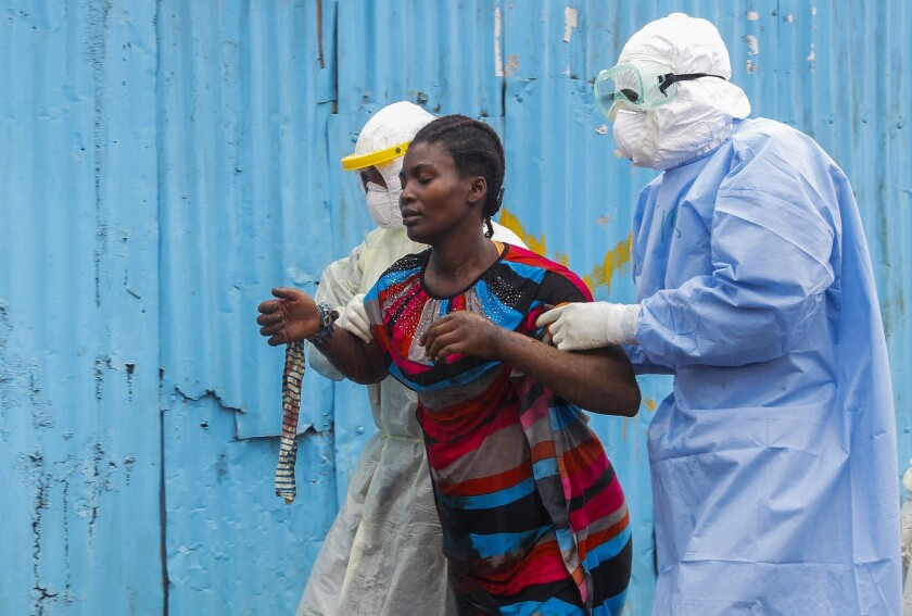 Nurses escort a suspected Ebola patient into a treatment center in Monrovia, Liberia. The CDC says the number of Ebola cases in Liberia and Sierra Leone, the two hardest-hit countries, could reach 550,000 to 1.4 million by late January, if efforts to control the disease aren't stepped up.