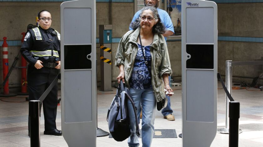 LOS ANGELES, CA - AUGUST 16, 2017: Metro passenger Morena Blanco walks through the scanner with item