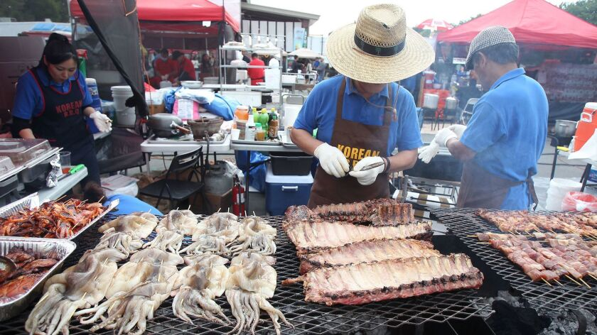 Cooks from the Lucky Ball Korean barbecue prepare the grill for hundreds of people during the OC Nig