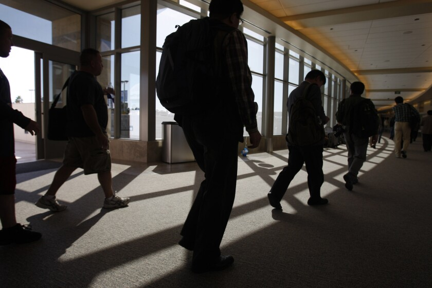 Travelers pass through John Wayne Airport in 2011. A man who allegedly told federal agents he was traveling overseas hoping to join Al Qaeda breakaway group ISIS was arrested at the airport July 2.