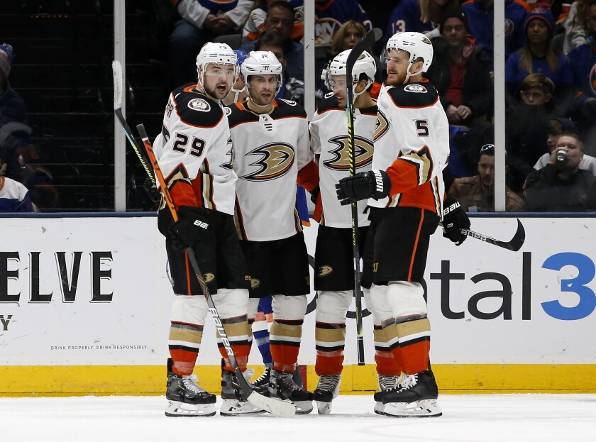 Ducks center Adam Henrique (14) celebrates a goal against the Islanders with teammates Devin Shore (29), Michael Del Zotto (44) and Korbinian Holzer (5) during the second period of a game Dec. 21.