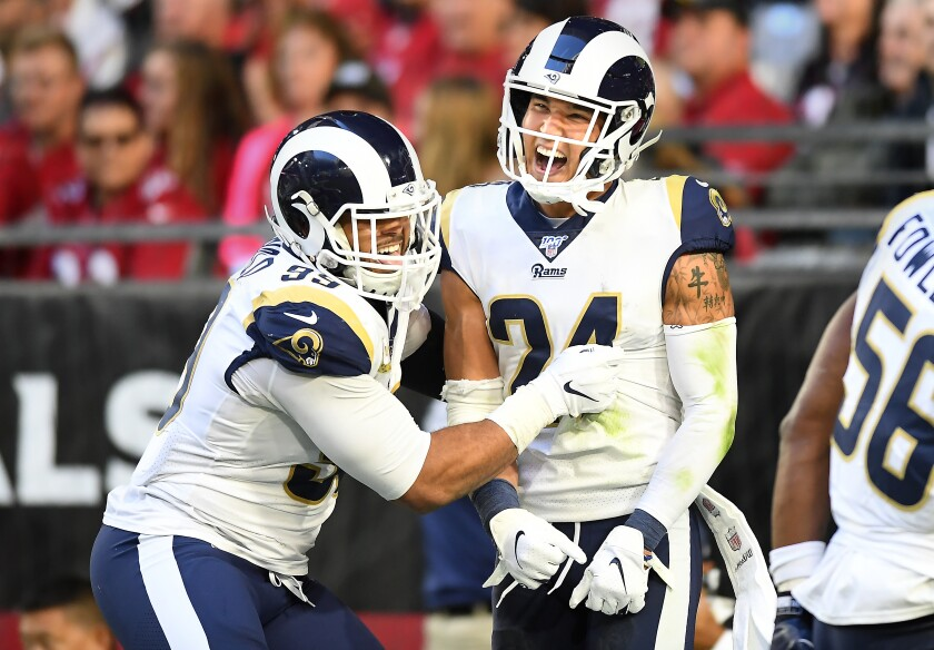 Aaron Donald congratulates Rams safety Taylor Rapp (24), who celebrates his interception return for a touchdown against the Cardinals in the third quarter.