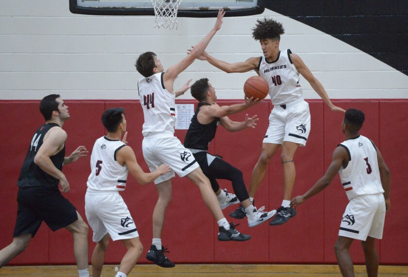 Spencer Hubbard of Harvard-Westlake drives to the basket as Corona Centennial's Payden White (40) and Mason Machado converge on him during the Wolverines' road victory on Tuesday night.