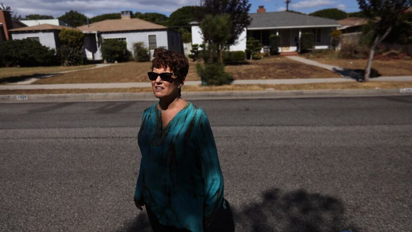 Karen Pomer, 63, a local political activist, stands across the street from a Santa Monica home where she sought help 23 years ago after being abducted and raped at gunpoint.