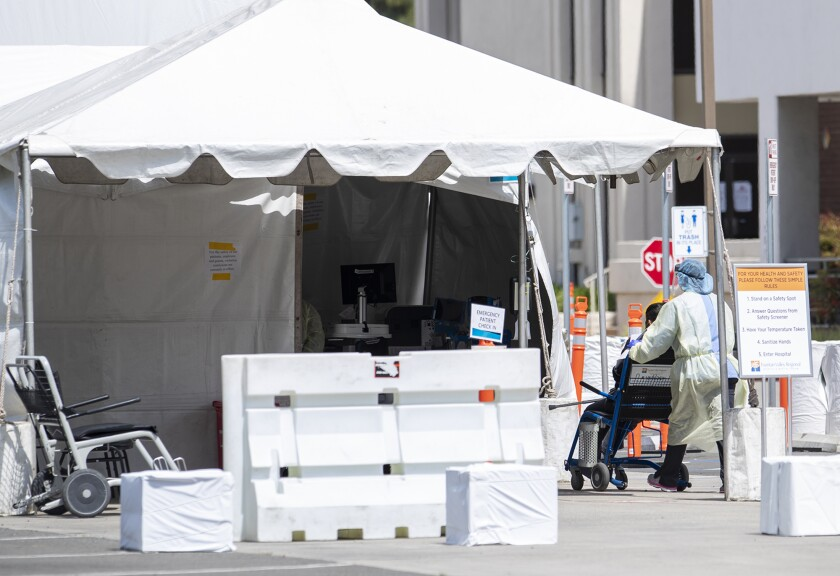 A medical professional wheels a patient into a tent outside the emergency room of Fountain Valley Regional Hospital & Medical Center on Thursday.