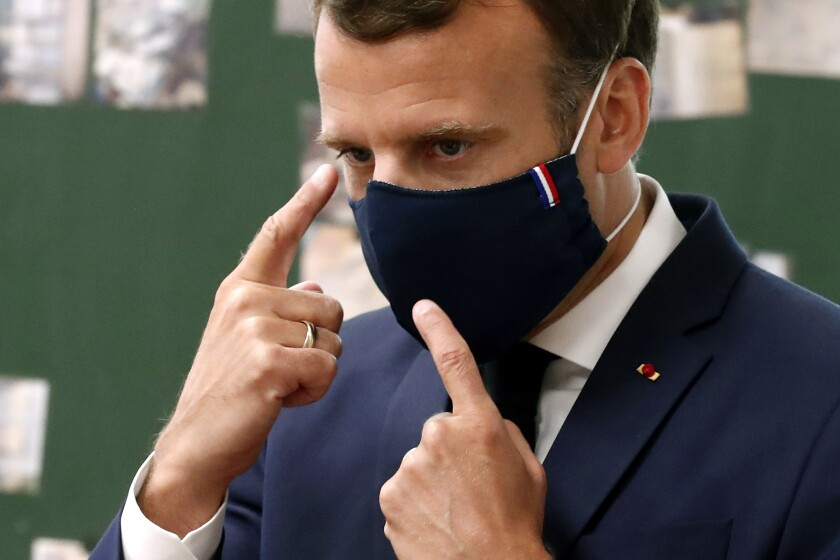 French President Emmanuel Macron wears a protective mask as he speaks with students at an elementary school outside Paris.