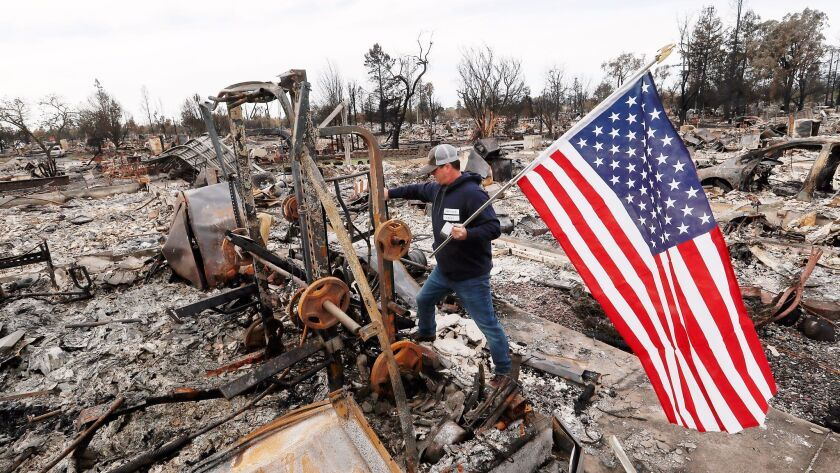 SANTA ROSA, CALIF. - OCT. 20, 2017. Jason Miller, 45, plants an American flag on the charred remai