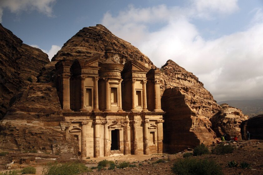 In this Feb. 23, 2016 photo, sun peaks out of rain clouds to light up the famous monastery in Petra southern Jordan. The Nabatean ruins are famous worldwide. (AP Photo/Sam McNeil)