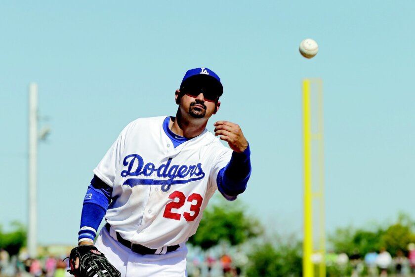 Los Angeles Dodgers first baseman Adrian Gonzalez tosses a ball to a fan in an exhibition spring training baseball game against the Cincinnati Reds Friday, March 22, 2013, in Glendale, Ariz. (AP Photo/Mark Duncan)