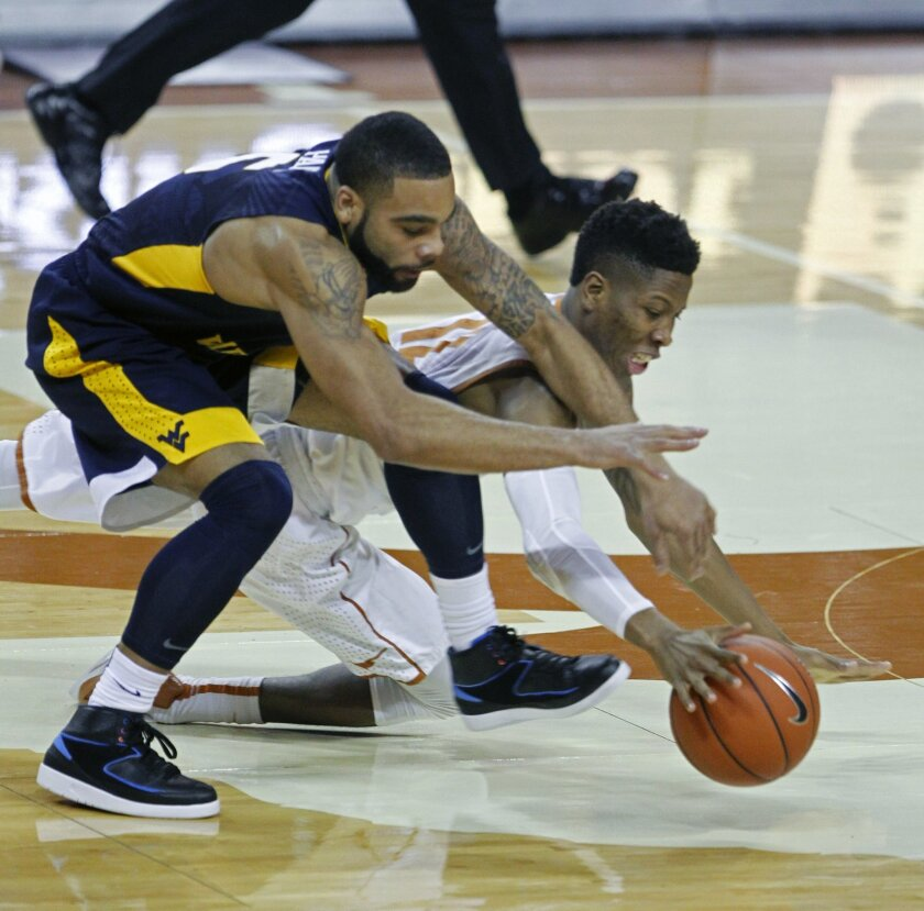 Texas guard Kerwin Roach, right, fights for the loose ball against West Virginia guard Jaysean Paige, left, during the first half of an NCAA college basketball game, Tuesday, Feb. 16, 2016, in Austin, Texas. (AP Photo/Michael Thomas)